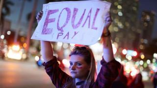 Mujer sostiene un cartel reclamando salario igualitario
