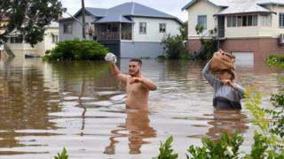 Two people wade through waist-deep water in Lismore.