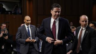 James Comey gets up to leave after giving testimony to the Senate Intelligence Committee