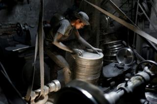 A boy works at an aluminium utensils factory in Dhaka, Bangladesh