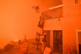 Bomberos agarran una bandera de EEUU