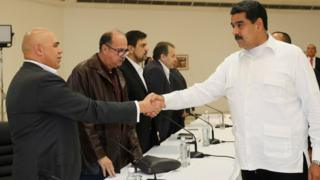 President Nicolas Maduro (R) shakes hands with opposition leader Jesus Torrealba during political meeting between government and opposition, in Caracas, Venezuela October 30, 2016