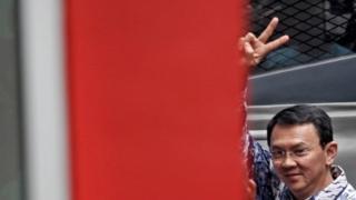 Basuki Tjahaja Purnama raises his hand as he arrives at the Cipinang prison in Jakarta, 9 May