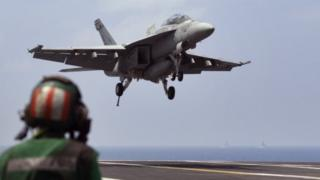 A US Navy fighter jet approaches to land on the aircraft carrier USS Theodore Roosevelt (17 October 2015)