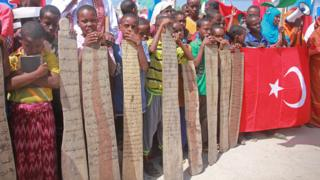 Women hold a Turkish flag, and young children display verses of the Koran written on wooden planks as they join Somalis protesting against an attempted military coup in Turkey, in Mogadishu, Somalia, Saturday, 16 July 2016