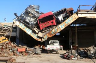 Damaged vehicles pile on a damaged roof of a car mechanic service center in Ramousah area southwest of Aleppo, Syria