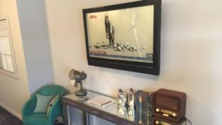 A mock television shows a painting by Banksy - a girl throwing rocks at the camera, apparently on the CNN channel. But the glass of the fake television is itself broken by her assault.