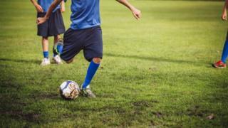A boy kicking a football
