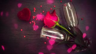 Unas copas de champaña con una rosa roja y unos corazones