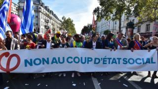 "Protesters hold a banner reading ""no to the social coup d'etat"" during a demonstration against the French governments labour reforms in Paris, 23 September 2017"