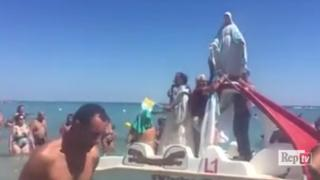 A priest blesses bathers from the back of a seaside pedalo