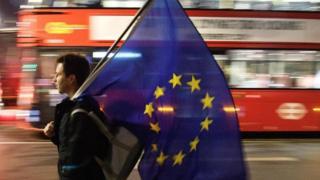 Una persona caminando con una bandera de la Unión Europea. Al fondo, un tradicional autobús de dos pisos británico pasa