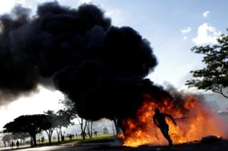 A demonstrator runs near a burning barricade during a protest against President Michel Temer in Brasilia