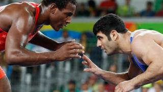 In this file photo taken on August 20, 2016 shows USA's J'den Michael Tbory Cox (red) wrestling with Iran's Alireza Mohammad Karimi Mashiani during the wrestling event of the Rio 2016 Olympic Games