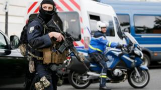 A masked and armed special forces member secures the street outside the courthouse during the departure of Paris attacks suspect Salah Abdeslam in Paris, France (20 May 2016