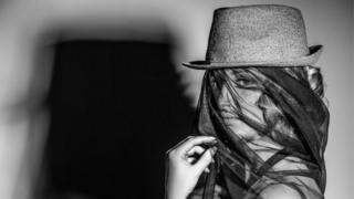 Una modelo con un sombrero y un velo