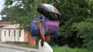 A Burundian woman carries her belongings on her head in Bujumbura, Burundi, Saturday, Nov. 7, 2015.