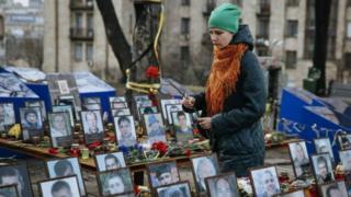 Дівчина з квітами біля фотографій загиблих