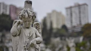 Head stones adorn graves in a Roman Catholic cemetery below residential buildings in Hong Kong (18 December 2012)