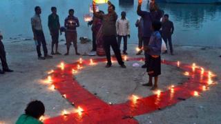 أشخاص يشعلون الشموع في اليوم العالمي للإيدز