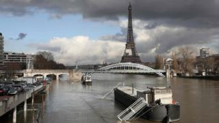 A picture taken on January 26, 2018, shows the flooded banks of the river Seine with the Eiffel Tower in the background in Paris.