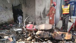 Pakistani rescue workers search the site of a suicide bomb attack on the outskirts of Peshawar (19 January 2016)