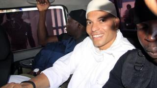Karim Wade, son of former Senegalese President Abdoulaye Wade, arrives at a courthouse in Dakar, Senegal, flanked by two prison guards on July 31, 2014,