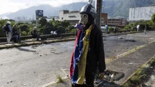 A Venezuelan protester stands in the street wearing a gas mask