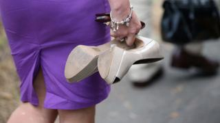 ผู้หญิงถือรองเท้าส้นสูง