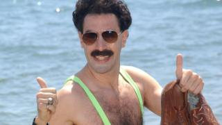 Sacha Baron Cohen as Borat in a mankini with thumbs up