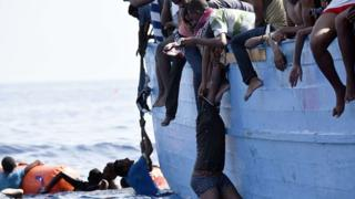 Migrant dey hang from boat near Libya, on October 4, 2016.