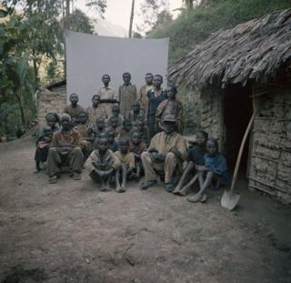 A group sit in front of a backdrop.