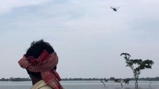 हेलीकॉप्टर देखते एक बाढ़ पीड़ित