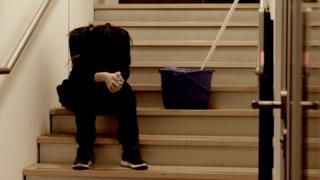 Mulher sentada em escadaria próxima a utensílios usados em faxina