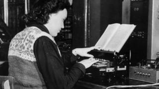 Woman types at a typewriter