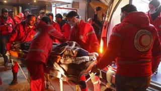 Volunteers from the Syrian Arab Red Crescent load a sick civilian into an ambulance in Douma on the third night of evacuations from the besieged rebel enclave of eastern Ghouta on the outskirts of the capital Damascus late on December 28, 2017