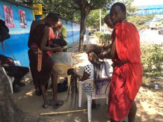 Masaai men braid a customer's hair