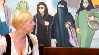 A woman studies a mural of women wearing Muslim veils at a beer tent in Munich, Bavaria, during the Oktoberfest festival on 15 September 2016