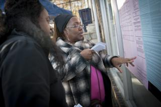 A volunteer talks about ballot measures with a voter outside a polling location for the 2016 US presidential election after polls opened at Wright's Barber Shop in Philadelphia, Pennsylvania, 8 November
