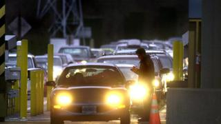 A US Customs officer (R) is on duty as cars line up to pass through the customs station at Blaine, Washington to enter Surrey, Canada 20 December 1999, as the wait to cross the border increased in the wake of the manhunt for a possible accomplice of an Algerian terrorist in custody in Canada.