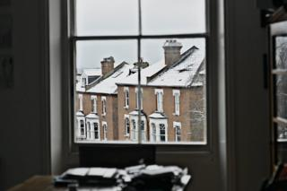 view of snowy rooftops through window