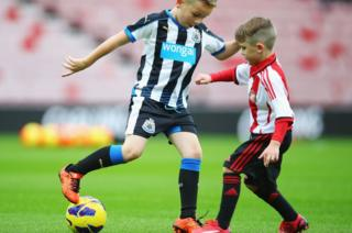 Two young footballers in Newcastle and Sunderland strips