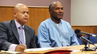 OJ seated beside his lawyer