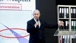 Israeli Prime Minister Benjamin Netanyahu on stage presenting documents allegedly stolen from Iran's nuclear archives