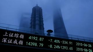 Chinese person holds umbrella whilst walking past boards showing stock price falls