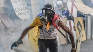 man in gas mask, draped in Venezuela flag, holding a mist can