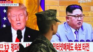 A South Korean soldier walks past a television screen showing pictures of US President Donald Trump (L) and North Korean leader Kim Jong Un