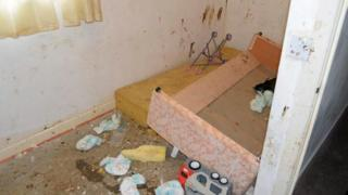 A child's bedroom with faeces on the wall and dirty nappies strewn across the floor
