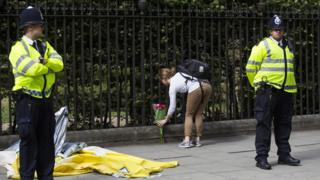 Woman lays flowers at scene of stabbing in Russell Square as police stand guard