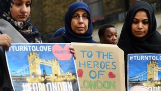 Muslim ladies hold placards at London vigil